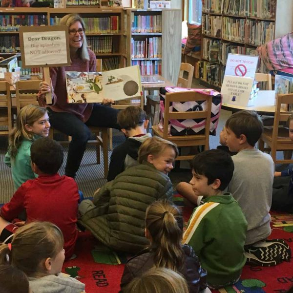 Author Courtney Spain Aragon reading Fraydo the Dragon to a group of children.